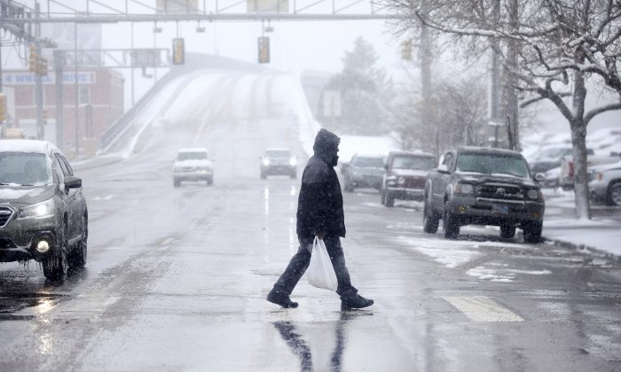 A pedestrian walks across Warren Avenue during a blizzard warning hitting southeast Wyoming and the Colorado Front Range in Cheyenne, Wyo., on April 10, 2019. (Jacob Byk/The Wyoming Tribune Eagle via AP)