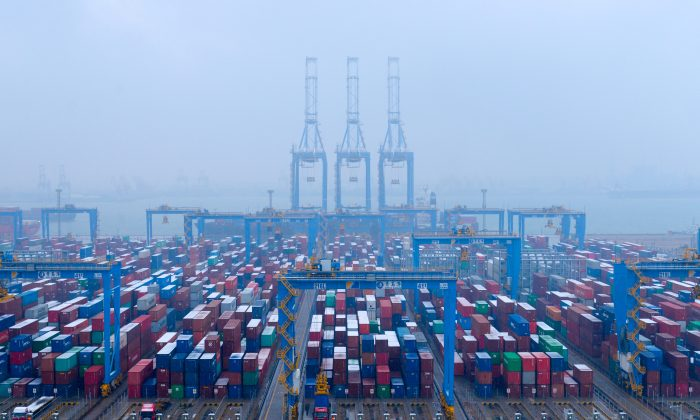 Containers and trucks are seen on a snowy day at an automated container terminal in Qingdao port, Shandong Province, China on Dec. 10, 2018. (Reuters)