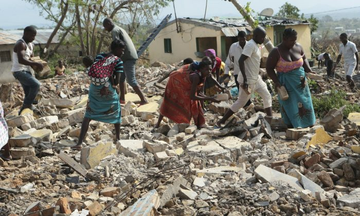 Women and men pick up bricks from a collapsed house to build another structure in Beira, Mozambique, on March, 31, 2019. (Tsvangirayi Mukwazhi/Photo via AP)