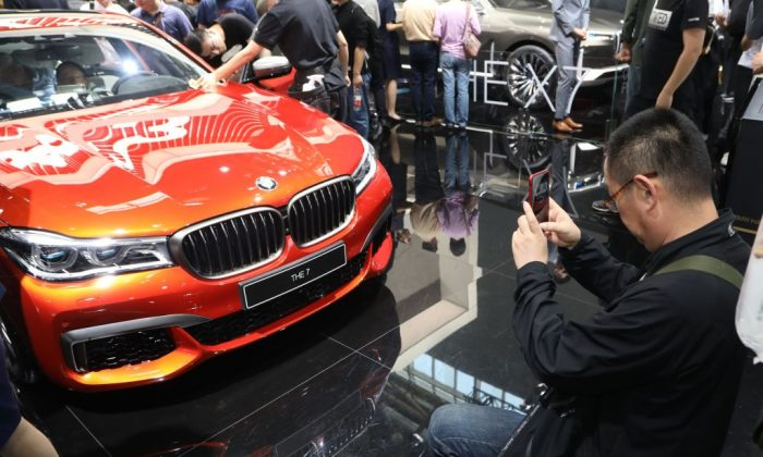 """A man takes a picture of a BMW """"THE 7"""" during the first public opening day at the Beijing auto show in Beijing on April 27, 2018. (AFP/Getty Images)"""