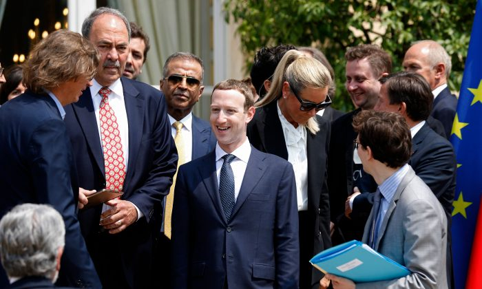 "Facebook's CEO Mark Zuckerberg (C) arrives for a family picture with guests of the ""Tech for Good"" Summit at the Elysee Palace in Paris, on May 23, 2018. CHARLES PLATIAU/AFP/Getty Images"