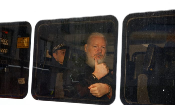 WikiLeaks founder Julian Assange is seen in a police van after was arrested by British police outside the Ecuadorian embassy in London, Britain on April 11, 2019. (Henry Nicholls/Reuters)