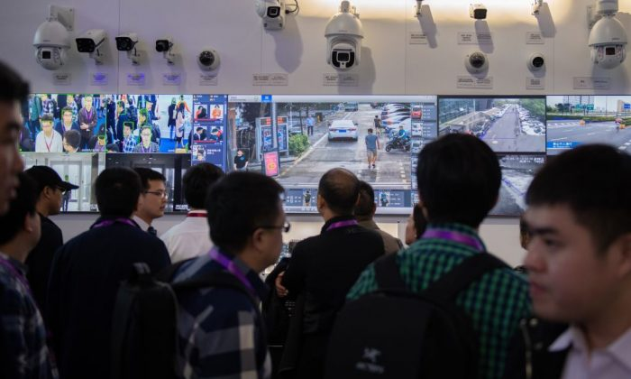 Visitors look at artificial-Intelligence security cameras using facial recognition technology at the 14th China International Exhibition on Public Safety and Security at the China International Exhibition Center in Beijing on Oct. 24, 2018. (Nicolas Asfouri/AFP/Getty Images)