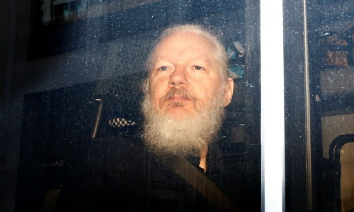WikiLeaks founder Julian Assange is seen in a police van, after he was arrested by British police, in London on April 11, 2019. (Henry Nicholls/Reuters)
