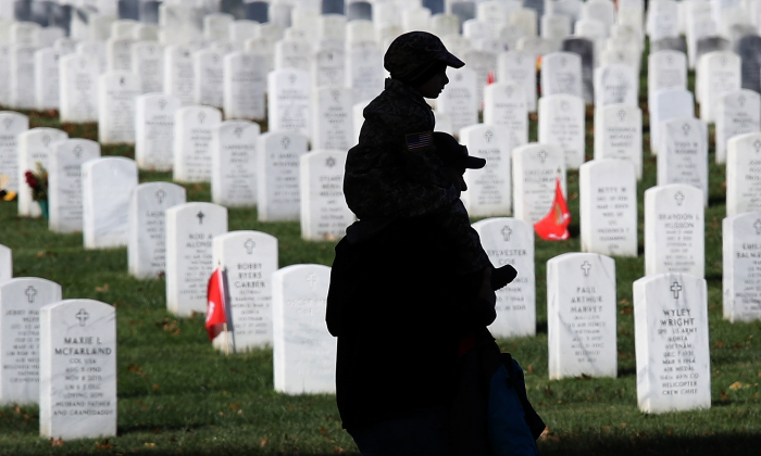 A young boy rides on his father's shoulders while visiting Arlington National Cemetery on Veterans Day Nov. 11, 2017 in Arlington, Virginia. (Win McNamee/Getty Images)