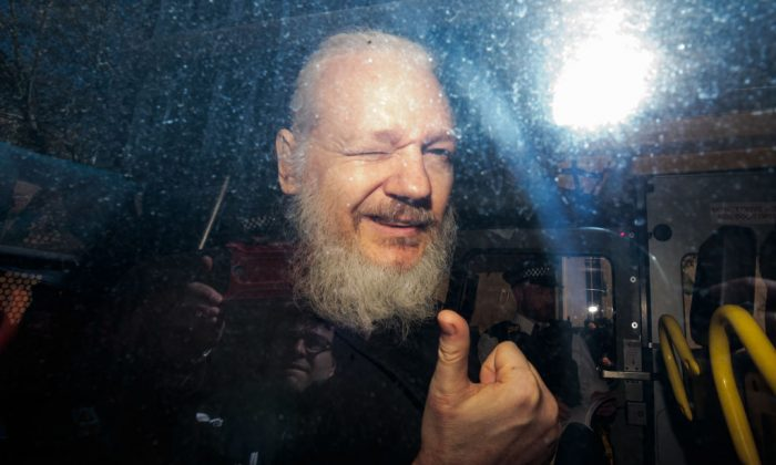 Julian Assange gestures to the media from a police vehicle on his arrival at Westminster Magistrates court on April 11, 2019 in London, England.  After weeks of speculation Wikileaks founder Julian Assange was arrested by Scotland Yard Police Officers inside the Ecuadorian Embassy in Central London this morning. Ecuador's President, Lenin Moreno, withdrew Assange's Asylum after seven years citing repeated violations to international conventions. (Jack Taylor/Getty Images)