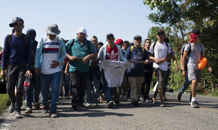 Central American migrants, part of a caravan hoping to reach the United States border, walk on a road in Frontera Hidalgo, Mexico, on April 12, 2019. (Isabel Mateos/Photo via AP)