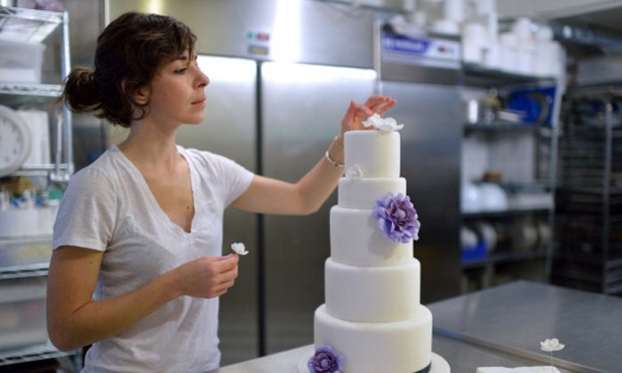An employee of Sugarplum cake shop decorates a wedding cake for US residents in France in Paris, on October 26, 2012 .(Photo by ERIC FEFERBERG/AFP/Getty Images)