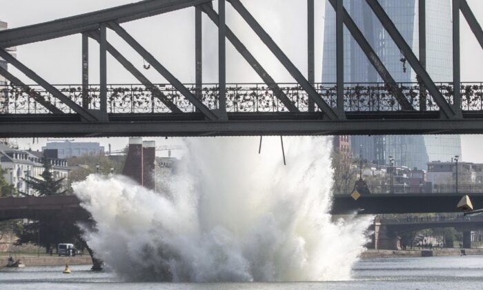 A large water fountain rises behind the Iron Bridge when a bomb from the Second World War in the Main River is detonated with a blast in Frankfurt, Germany, on April 14, 2019. (Frank Rumpenhorst/dpa via AP)