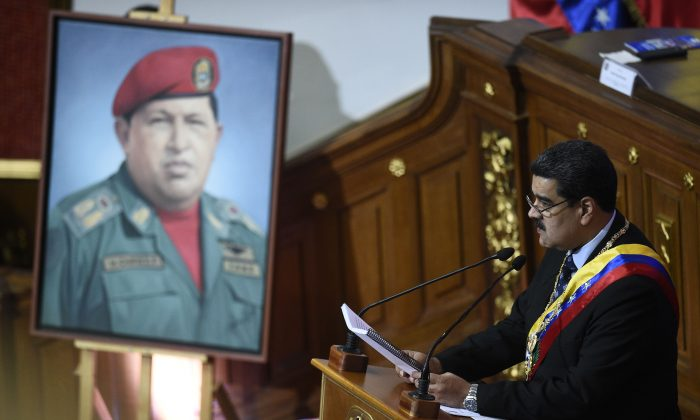 Venezuelan President Nicolas Maduro speaks before the Constituent Assembly near a portrait of late Venezuelan President Hugo Chavez to announce measures to alleviate the serious economic crisis, at the Federal Legislative Palace in Caracas on Jan. 14, 2019. (FEDERICO PARRA/AFP/Getty Images)