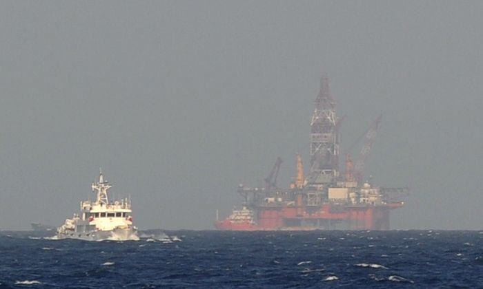 A Chinese coast guard vessel (L) sails near China's oil drilling rig in disputed waters in the South China Sea on May 14, 2014. (HOANG DINH NAM/AFP/Getty Images)