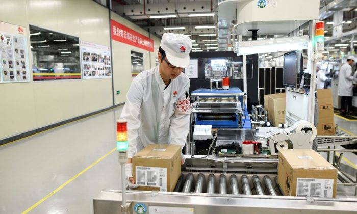 An employee works on a mobile phone production line at a Huawei production base during a media tour in Dongguan, China's Guangdong province on March 6, 2019. (WANG ZHAO/AFP/Getty Images)