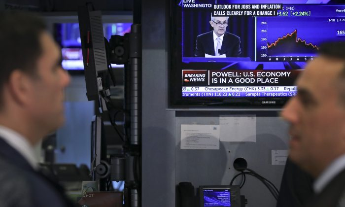 Traders watch as a monitor displays news about the Fed's decision not to change interest rates, on the floor of the New York Stock Exchange (NYSE) in New York City on March 20, 2019. (Drew Angerer/Getty Images)
