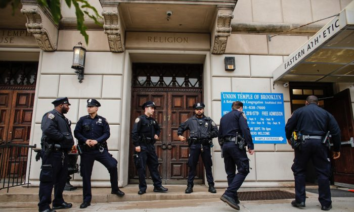 NYPD officers stand guard at the door of the Union Temple of Brooklyn in New York on Nov. 2, 2018. Police determined that anti-Semitic graffiti found inside a Brooklyn synagogue was scrawled by a former city council intern. (Kena Betancur/AFP/Getty Images)