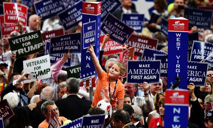 """Delegates hold up signs that read """"Make America First Again"""" at the Republican National Convention at the Quicken Loans Arena in Cleveland, Ohio, on July 20, 2016. Jeff J Mitchell/Getty Images"""