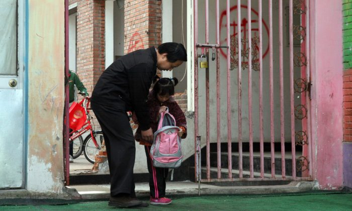 A father picking up his daughter from kindergarten. (STR/AFP/GettyImages)