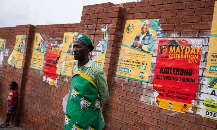 A man stands against a wall covered with election campaign ads on April 11, 2019, in Alexandra, South Africa. (Wikus de Wet/AFP/Getty Images)
