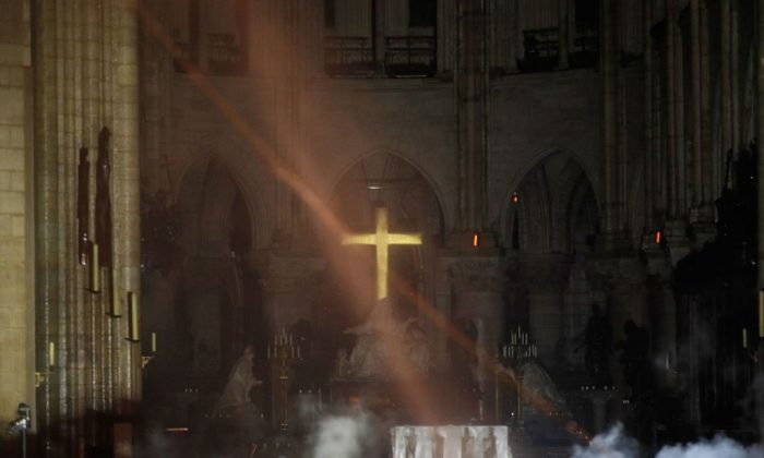 Smoke rises around the alter in front of the cross inside the Notre-Dame Cathedral as the fire continues to burn in Paris on April 16, 2019. (Philippe Wojazer/AFP/Getty Images)