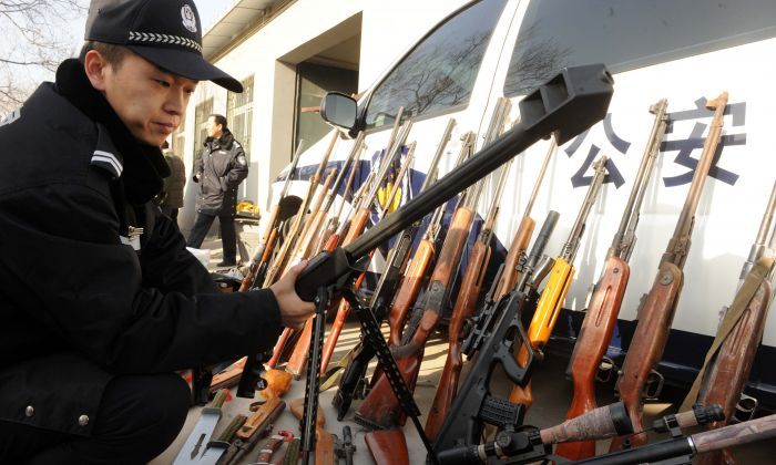 Chinese police prepare to destroy some 900 firearms and ammunition seized over the last nine months in Beijing on December 16, 2010. (STR/AFP/Getty Images)