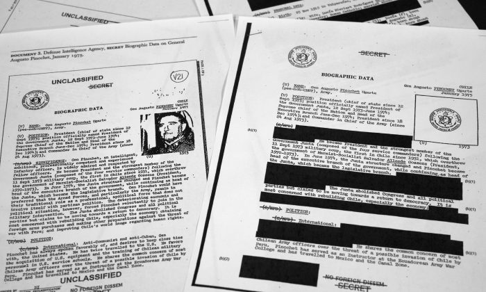 The redacted, right, and the unredacted versions of the biographical intelligence file report on Chilean dictator Augusto Pinochet from 1975 is photographed in Washington on April 15, 2019. (AP Photo/Jon Elswick)