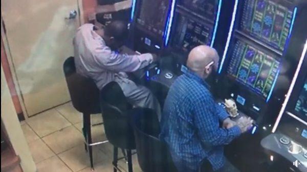 suspect reaches into the machine