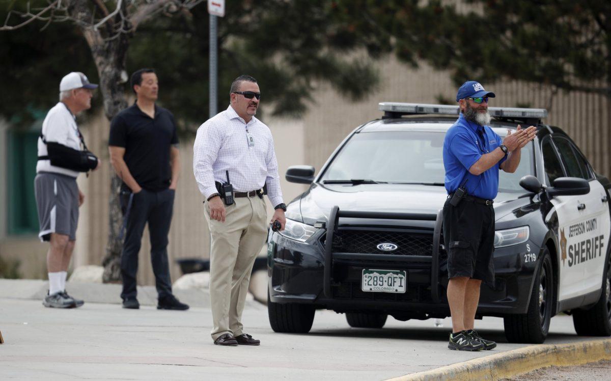 School police officers look on as students leave Columbine High School
