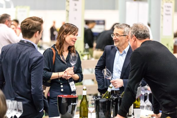 people hold wine glasses and talk at vinexpo new york