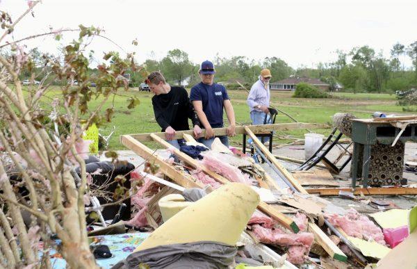 Men clean up house debris at Hamilton, Mississippi, on April 14, 2019.