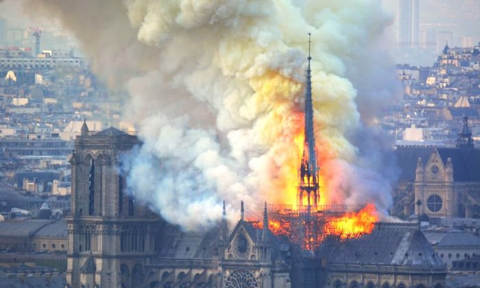 TOPSHOT - Smoke and flames rise during a fire at the landmark Notre-Dame Cathedral in central Paris on April 15, 2019, potentially involving renovation works being carried out at the site, the fire service said. - A major fire broke out at the landmark Notre-Dame Cathedral in central Paris sending flames and huge clouds of grey smoke billowing into the sky, the fire service said. The flames and smoke plumed from the spire and roof of the gothic cathedral, visited by millions of people a year, where renovations are currently underway. (Photo by Hubert Hitier / AFP)        (Photo credit should read HUBERT HITIER/AFP/Getty Images)