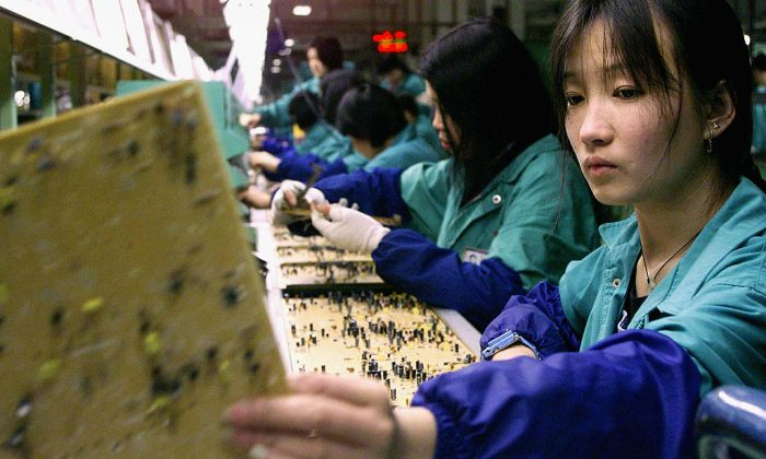 Workers inspect data boards at a Taiwanese factory in China's Fujian province. (STEPHEN SHAVER/AFP/Getty Images)