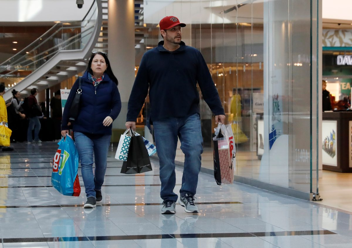 People walk with shopping bags at Roosevelt Field mall in Garden City