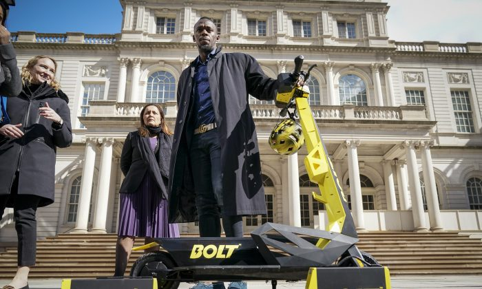 Track star and new Bolt pitchman Usain Bolt poses for photos with a Bolt Mobility scooter outside of New York City Hall following a press conference about the new product, Mar. 12, 2019 in New York City. (Drew Angerer/Getty Images)