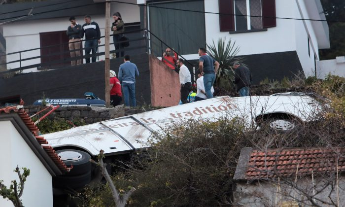 People stand next to the wreckage of a bus after an accident in Canico, in the Portuguese Island of Madeira, April 17, 2019. (Duarte Sa/Reuters)