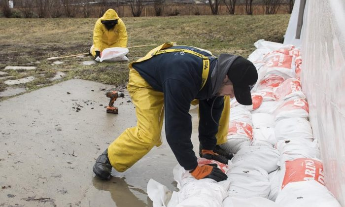 A man places a sandbag next to the foundation of a house in the town of Hudson, Que. west of Montreal, on April 19, 2019. (The Canadian Press/Graham Hughes)