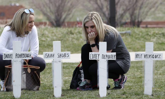 Cassandra Sandusky (R) a graduate of Columbine High School, pauses at a row of crosses bearing the names of the victims of the attack at the school 20 years ago before a remembrance for the victims in Littleton, Colo. on April 20, 2019. (David Zalubowski/AP Photo)
