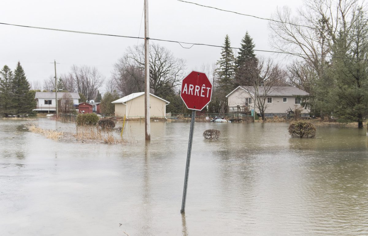 A residential street is shown surrounded by floodwaters