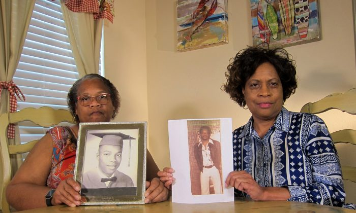 Mylinda Byrd Washington, 66 (R) and Louvon Byrd Harris, 61, hold up photographs of their brother James Byrd Jr. in Houston, on April 10, 2019. (Juan Lozano/AP)