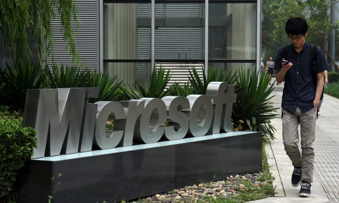 A man walks past a Microsoft sign outside a Microsoft office building in Beijing on July 31, 2014. (Greg Baker/AFP/Getty Images)