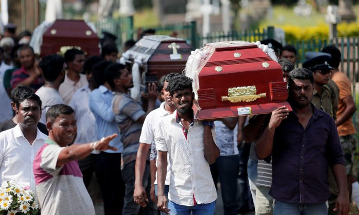 Coffins of victims are carried during a mass for victims, two days after a string of suicide bomb attacks on churches and luxury hotels across the island on Easter Sunday in Colombo, Sri Lanka, on April 23, 2019. (Dinuka Liyanawatte/Reuters)