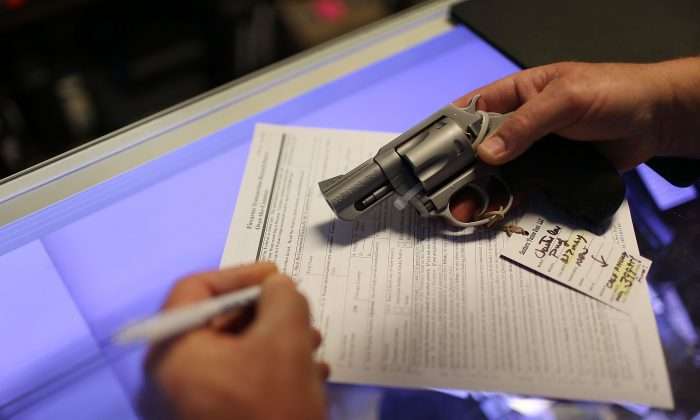 A customer fills out his federal background check paperwork as he purchases a handgun in Delray Beach, Fla., on Jan. 5, 2016. (Joe Raedle/Getty Images)