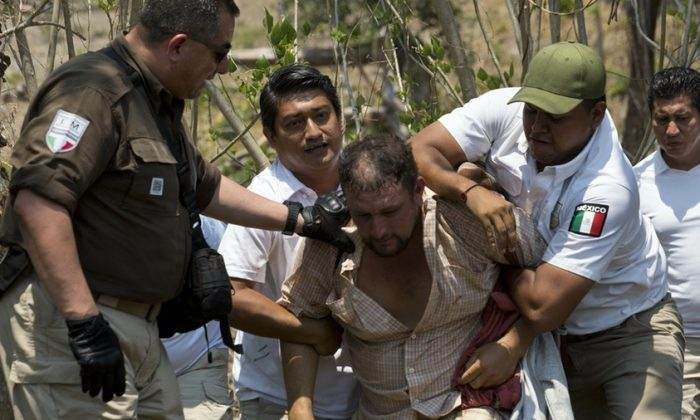 A Central American migrant is detained by Mexican immigration agents on the highway to Pijijiapan, Mexico, on April 22, 2019.  (Moises Castillo/AP Photo)
