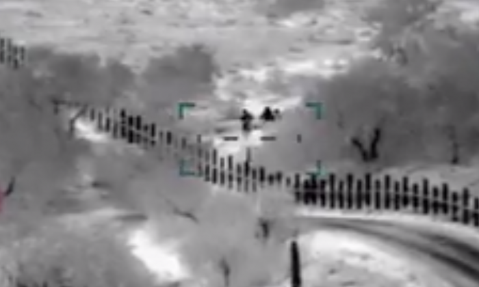 U.S. Customs and Border Patrol released a video showing armed men escorting a woman and her son across the U.S. border on April 20, 2019. (CBP)