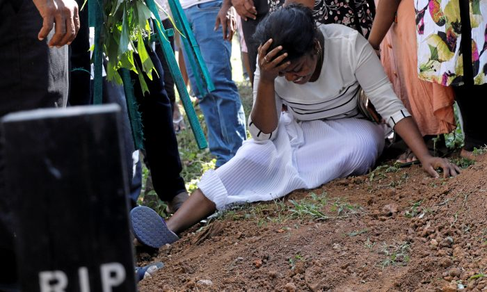 A woman during a mass burial of victims, two days after a string of suicide bomb attacks on churches and luxury hotels across the island on Easter Sunday, in Colombo, Sri Lanka, on April 23, 2019. (Dinuka Liyanawatte/Reuters)