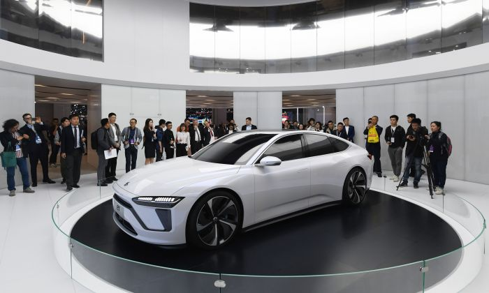 Visitors look at a Nio ET Preview car on the opening day of the Shanghai Auto Show in Shanghai on April 16, 2019. (GREG BAKER/AFP/Getty Images)