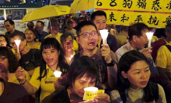 "Pro-democracy supporters attend candlelight vigils to support four jailed leaders of the 2014 pro-democracy ""Occupy"" movement, also known as ""Umbrella Movement,"" outside Lai Chi Kok Reception Center in Hong Kong, China on April 24, 2019. (Tyrone Siu/Reuters)"