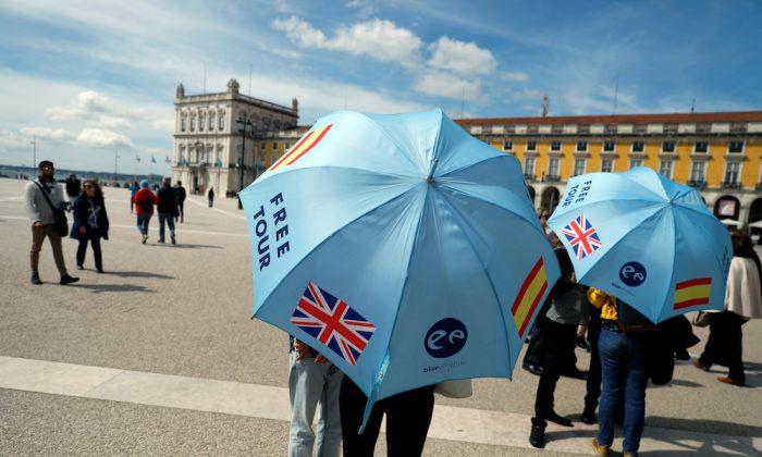 Tour guides wait for tourists at Comercio square in downtown Lisbon, Portugal, on April 11, 2019. (Rafael Marchante/Reuters)
