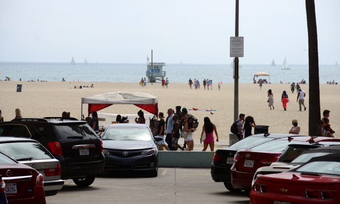 People walk on the Venice Beach boardwalk on Aug. 4, 2013. (Robyn Beck/AFP/Getty Images)