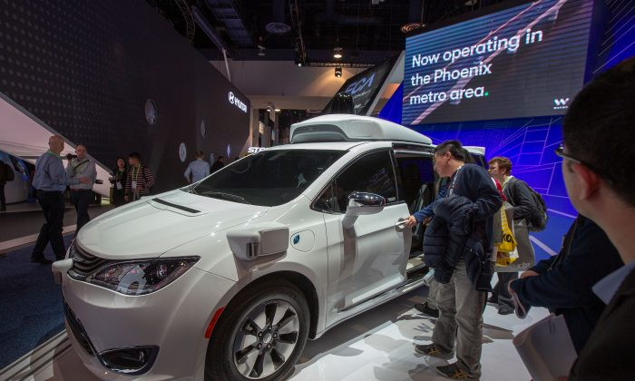 People look at the Waymo car, formerly the Google self-driving car project, during the Las Vegas Convention Center during CES 2019 in Las Vegas on Jan. 9, 2019. (David McNew/AFP/Getty Images)