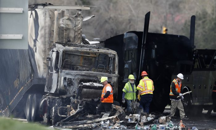 """Workers clear debris from the eastbound lanes of Interstate 70 on Friday, April 26, 2019, in Lakewood, Colo., a deadly pileup involving semi-truck hauling lumber on Thursday. Lakewood police spokesman John Romero described it as a chain reaction of crashes and explosions from ruptured gas tanks. """"It was crash, crash, crash and explosion, explosion, explosion,"""" he said. (AP Photo/David Zalubowski)"""