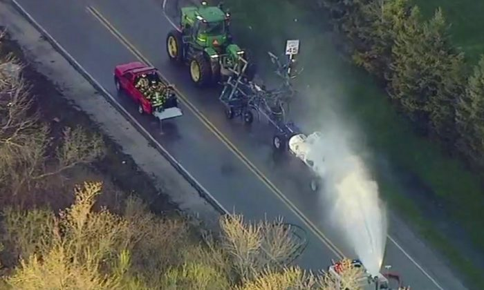 In this still image from video provided by ABC7 Chicago, a fire engine sprays water on a container of the chemical that farmers use for soil after after anhydrous ammonia leaked in Beach Park, Ill., on April 25, 2019. (ABC7 Chicago via AP)